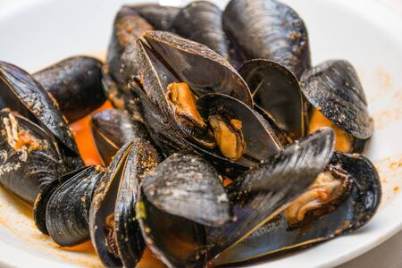 pics: A dish of  mussels pics with tomato sauce, open, ready to eat, in a table spread. Stock Photo
