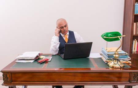 important phone call: A business man on the phone and pc, at desk, in conference call and bald. An antique desk and important.