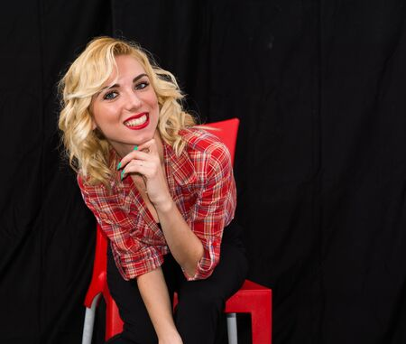 long pants: Young girl, pin up typical American. With pants or leggings and long blacks, on a black background, red and white checkered shirt, knotted navel, features dazzling smile. Stock Photo