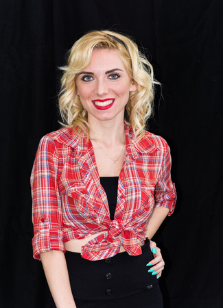 Young girl, pin up typical American. With pants or leggings and long blacks, on a black background, red and white checkered shirt, knotted navel, features dazzling smile. Stock Photo