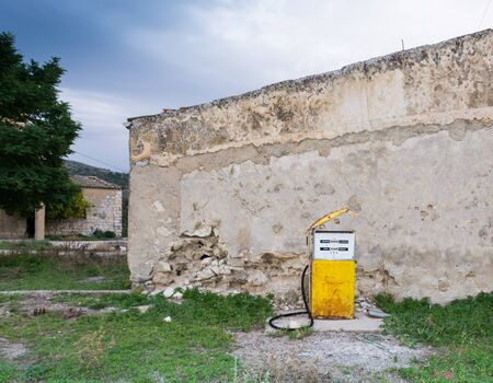 fueling pump: Distributor or gas pump, abandoned. Isolated, old and rusty in a war zone, a symbol of power, the concept of abandonment. Abstract pollution. Old gas station. In war zones. Stock Photo