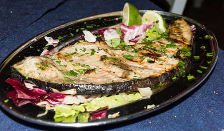 lombriz: A swordfish dishes pics, among lemons cut, on a glass dish, over a bed of lettuce, ready to eat, in a table spread.