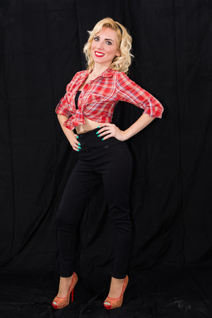 dazzling: Young girl, pin up typical American. With pants or leggings and long blacks, on a black background, red and white checkered shirt, knotted navel, features dazzling smile. Stock Photo