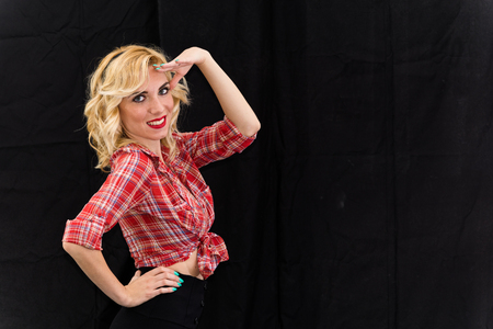 blacks: Young girl, pin up typical American. With pants or leggings and long blacks, on a black background, red and white checkered shirt, knotted navel, features dazzling smile. Stock Photo