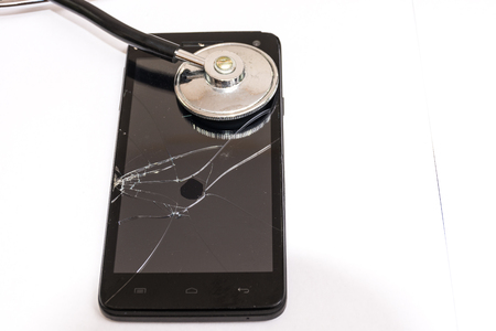 broken back: Black smartphone with broken glass and stethoscope. Concept of care needs, to repair. In abstract broken, you can not go back. Stock Photo