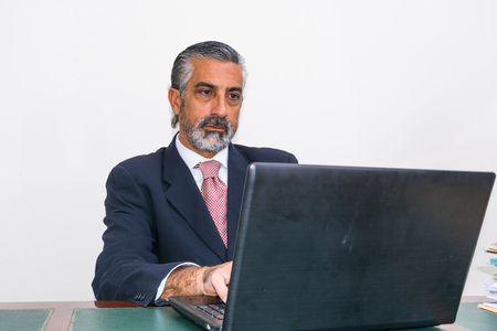 hair blacks: Businessman in a suit and tie, in his studio. At the desk, using pc.