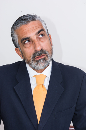 expresiones faciales: Adult man, mature, in suits. Bearded, grizzled, he thinks, deep in thought. Facial expressions, making faces. Foto de archivo