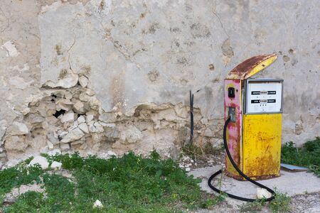 abandonment: Distributor or gas pump, abandoned. Isolated, old and rusty in a war zone, a symbol of power, the concept of abandonment. Abstract pollution. Old gas station. In war zones. Stock Photo