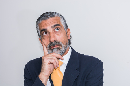 disheartened: Adult man, mature, in suits. Bearded, grizzled, he thinks, deep in thought. Facial expressions, making faces. Stock Photo