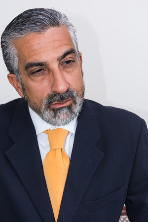 grizzled: Adult man, mature, in suits. Bearded, grizzled, he thinks, deep in thought. Facial expressions, making faces. Stock Photo