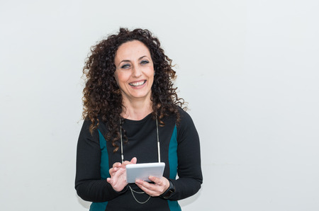 hair blacks: Modern mature woman, happy and smiling,  use the tablet. She has long curly hair and blacks, with green eyes. Cheerful and smiling.