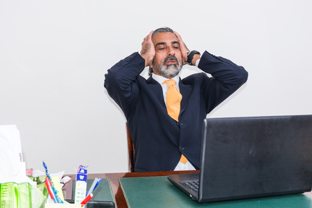 palpitations: Desperate businessman. Alone in his office, in front of the desk with the computer, it panic, depression.