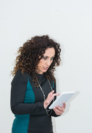 indignant: Modern mature woman, angry, use the tablet. She has long curly hair and blacks, with green eyes. Enraged, he gets angry with his work tool. Stock Photo