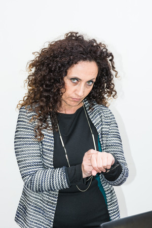 blacks: Modern mature woman, angry, use the smartwacth. She has long curly hair and blacks, with green eyes. Enraged, he gets angry with his work tool.
