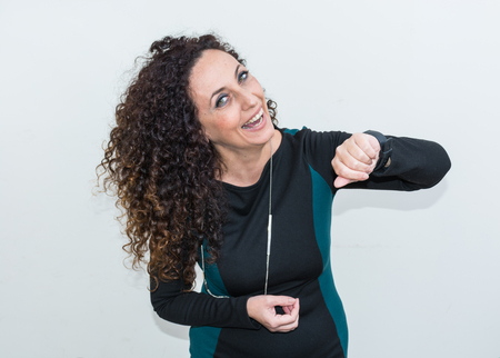 hair blacks: Modern mature woman, happy and smiling,  use the smartwacth. She has long curly hair and blacks, with green eyes. Cheerful and smiling. Stock Photo