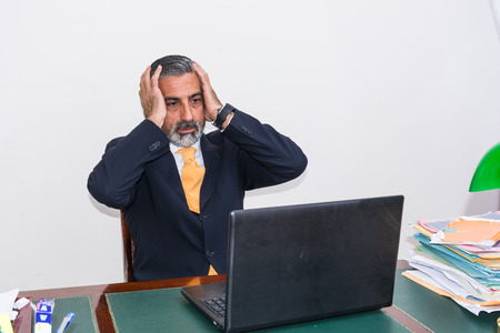 disheartened: Desperate businessman. Alone in his office, in front of the desk with the computer, it panic, depression.