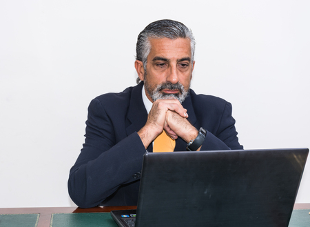 gray haired: Businessman in a suit and tie, in his studio. At the desk, using pc.