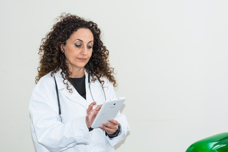 hair blacks: Doctor with curly hair and blacks and with green eyes, use a tablet of white color. The new technologies used in the medical field. Stock Photo