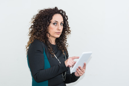 regenerated: Mature Woman modern use the tablet. She has long curly hair and blacks, with green eyes.