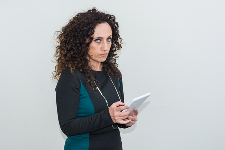 blacks: Modern mature woman, angry, use the tablet. She has long curly hair and blacks, with green eyes. Enraged, he gets angry with his work tool. Stock Photo