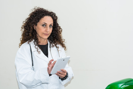 blacks: Doctor with curly hair and blacks and with green eyes, use a tablet of white color. The new technologies used in the medical field. Stock Photo