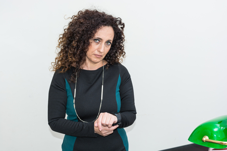 hair blacks: Mature Woman modern melancholy use the smartwacth. She has long curly hair and blacks, with green eyes.Melancholic, he becomes depressed with his work tool.