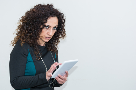 hair blacks: Modern mature woman, angry, use the tablet. She has long curly hair and blacks, with green eyes. Enraged, he gets angry with his work tool. Stock Photo