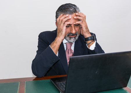 disheartened: Businessman in suit and tie, desperate, in his studio. Alone in his office, in front of the desk with the computer, it panic, depression.
