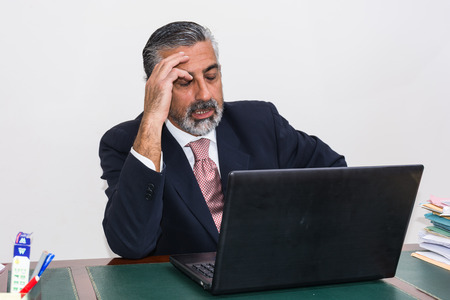 absorbed: Businessman in suit and tie, concentrated, in his studio. Alone in his office, in front of the desk with the computer, it pensive, absorbed. Stock Photo