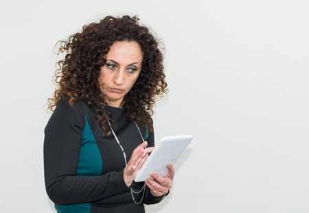 enraged: Modern mature woman, angry, use the tablet. She has long curly hair and blacks, with green eyes. Enraged, he gets angry with his work tool. Stock Photo