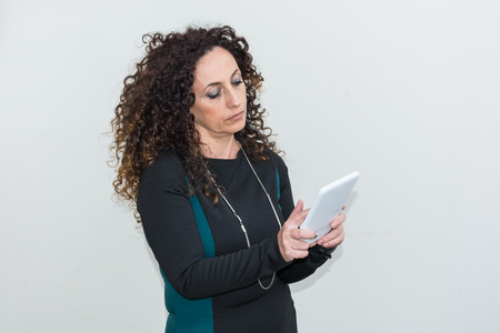 blacks: Mature Woman modern use the tablet. She has long curly hair and blacks, with green eyes.