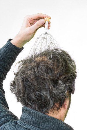 alternative therapy: Man relaxes with the Genie head massager. Alternative Therapy. Indian head massage tool, self head massager.