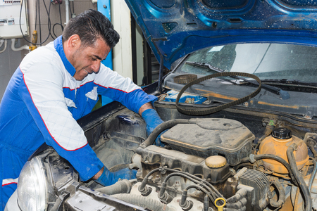 work gloves: Automotive specialist adjusting an engine in His garage, closeup of an experienced mechanic servicing a car at his workshop Stock Photo