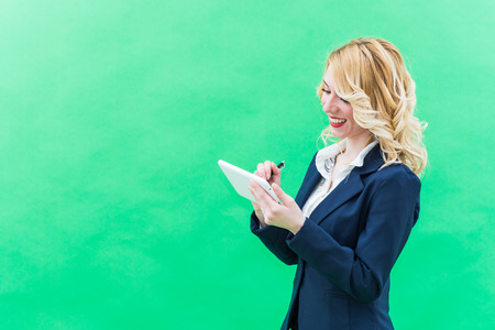 Young woman using tablet, standing. Wearing blue suit, she has blonde hair and blue or blue eyes, on a white background. Smile, always smiling.