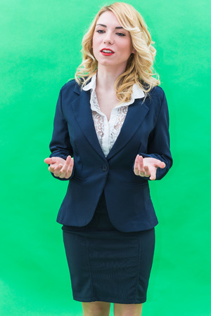 Young woman, standing, engaged in business education. Wearing blue suit, she has blonde hair and blue or blue eyes, on a white background. Smile, always smiling.
