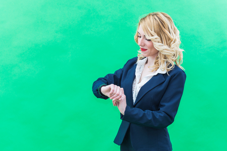 optimismo: Young woman using smartwacth, standing. Wearing blue suit, she has blonde hair and blue or blue eyes, on a white background. Smile, always smiling.