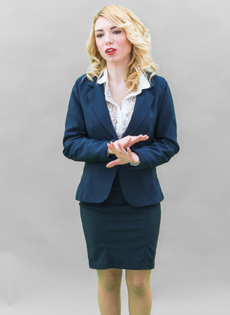 persuade: Young woman, standing, engaged in business education. Wearing blue suit, she has blonde hair and blue or blue eyes, on a white background. Smile, always smiling.