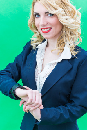 Young woman using smartwacth, standing. Wearing blue suit, she has blonde hair and blue or blue eyes, on a white background. Smile, always smiling.