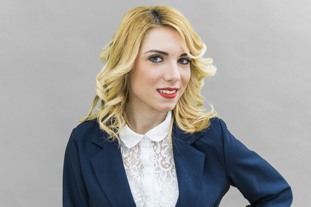 intriguing: Portrait of Young woman, in suits. Bearded, Wearing blue suit, she has blonde hair and blue or blue eyes, on a white background. Smile, always smiling.