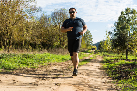 Grande pancia jogging uomo, che esercita, facendo cardio nel parco, un po 'sovrappeso, perdere peso. Su un prato di erba verde tra gli alberi senza foglie. Archivio Fotografico - 67035726