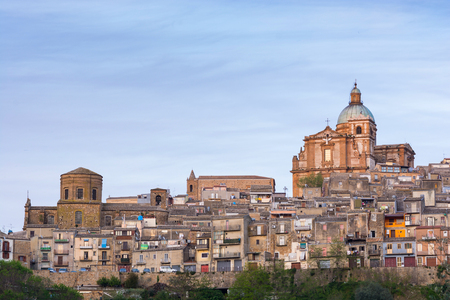 opulent: Ancient landscape of Piazza Armerina at sunset. From sunlight to night light passing through the blue hour. You see the baroque cathedral, Holy Mary of Victories in the foreground.