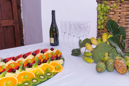 laden: Composition of fruit and cut glass demijohn coated for wine wicker. On a table laden with a restaurant, with grapes, figs, prickly pears and leaves. A bottle of wine, glasses.