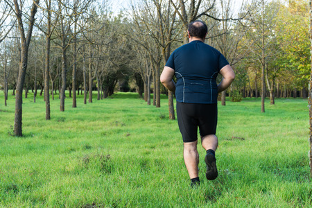Big belly man jogging , exercising, doing cardio in the park , slightly overweight, loosing weight. On a lawn of green grass between trees without leaves. Stock Photo