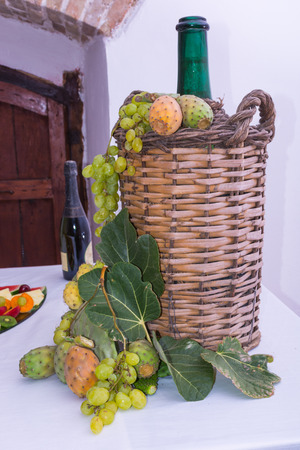 laden: glass carboy, lined wicker, for wine. On a table laden with a restaurant, with grapes, figs, prickly pears and leaves. A bottle of wine and glasses. Stock Photo