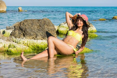 Girl on a rock in the sea, with a colorful hat with flowers and yellow swimsuit. Happy and smiling, the sun to get a tan, the beach between the rocks.