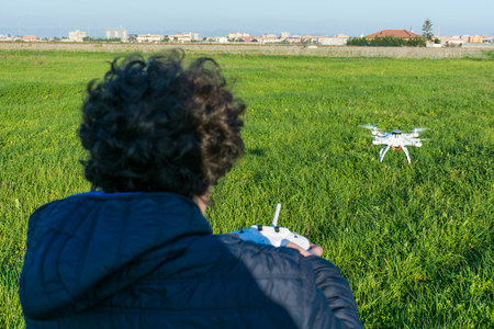 Abstract and conceptual child playing with a drone. Remote sensing. The happiness of a child with a toy modern and dangerous.