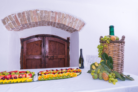 Composition of fruit and cut glass demijohn coated for wine wicker. On a table laden with a restaurant, with grapes, figs, prickly pears and leaves. A bottle of wine, glasses.