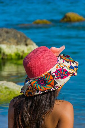 beach girl with colorful hat flowers and yellow swimsuit. Happy and smiling, sunbathing on the beach between the rocks.