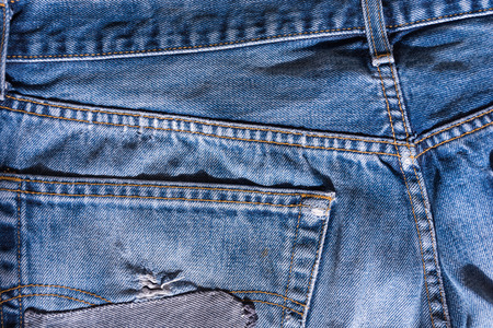fabric textures: Abstract and conceptual of blue jeans, or trousers with characteristic copper or metal rivets, with the central metal button, 5-pocket cut.
