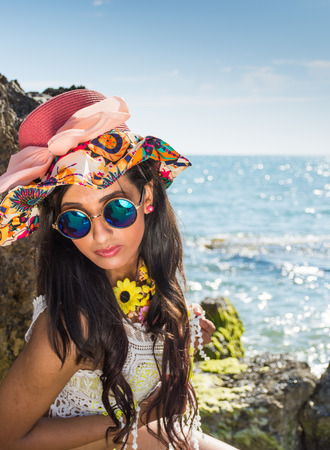 Girl on the rocks with colored hat flowers and yellow swimsuit. Happy and smiling, sunbathing sunbathing, the beach between the rocks. Stock Photo